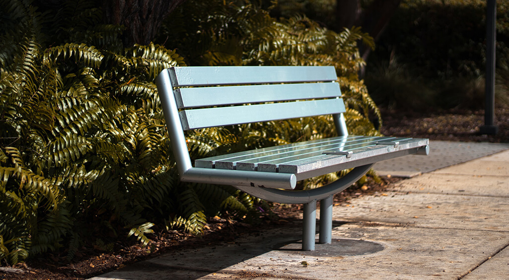 A park bench allows one or more people of different sizes to sit or recline comfortably